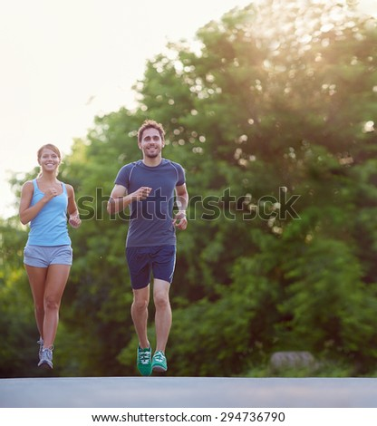 Young couple running together outdoors - stock photo