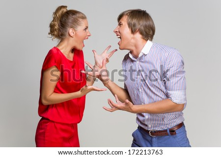 Young couple screaming at each other over grey background