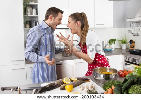 Young couple screaming at home in the kitchen. - stock photo