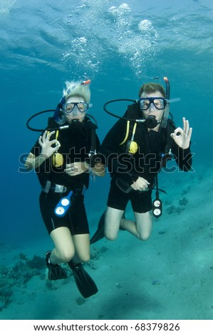 young couple scuba diver and give OK sign in the red sea - stock photo