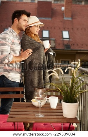 Young couple searching distance from balcony, embracing. - stock photo