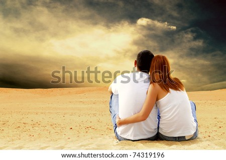 Young couple seating in desert in sunny day - stock photo