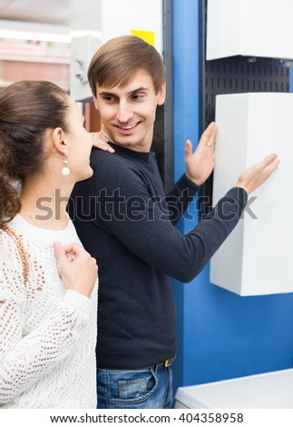 Young couple selecting heating water converter in household store