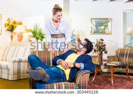 Young couple selecting together armchair in furniture store  - stock photo