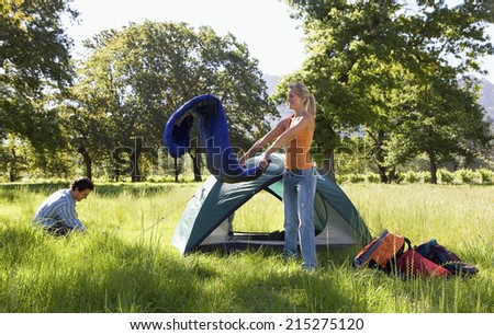 Young couple setting up camp in woodland clearing, woman unravelling rolled-up sleeping bag beside tent, side view - stock photo