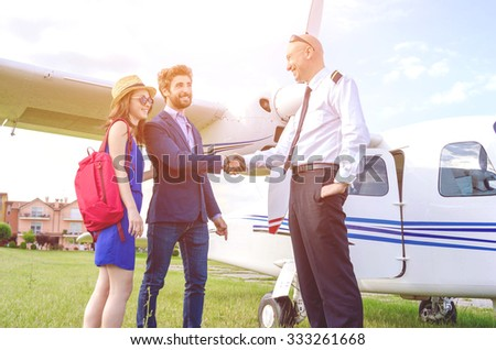 Young couple shaking hands with the pilot of a private plane during their vacation - Caucasian people - people, lifestyle and transportation concept - stock photo