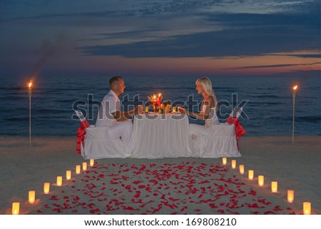 Young couple share a romantic dinner with candles, torches and way or rose petals at sea sandy beach against sunset - wedding day, proposal of marriage, St.Valentines Day or honeymoon concept