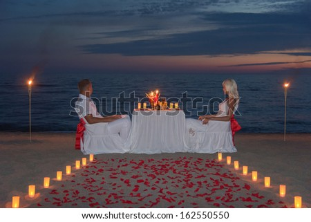 Young couple share a romantic dinner with candles, torches and way or rose petals on sea sandy beach against sunset - wedding day, proposal of marriage or honeymoon concept - stock photo