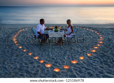Young couple share a romantic supper with candles heart on the sea sand beach - stock photo