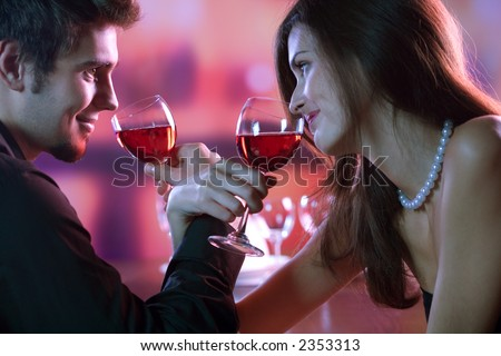 Young couple sharing a glass of red wine in restaurant, celebrating or on romantic date - stock photo