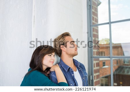 Young couple sharing a quiet moment at home standing in front of a large window staring out over the town below - stock photo