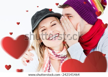 Young couple sharing a secret against hearts - stock photo