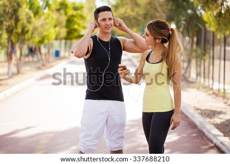 Young couple sharing some playlists between their smartphones before working out together - stock photo