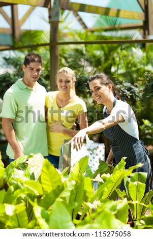 young couple shopping for plants in greenhouse - stock photo