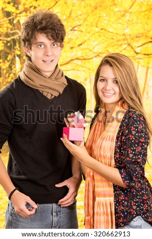 Young couple showing their love for camera posing, girl wearing flower pattern dark shirt, guy with black sweater, beige scarf, both brown hair.