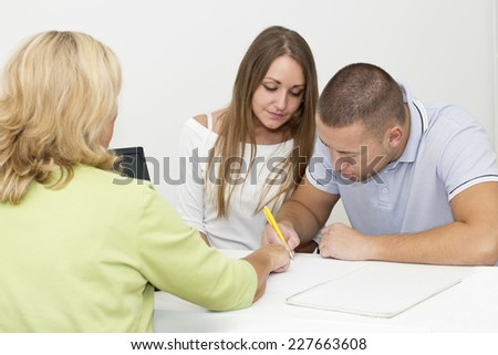 Young couple signing a contract during meeting  with financial advisor. - stock photo
