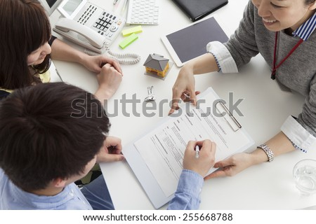Young couple signing financial contract