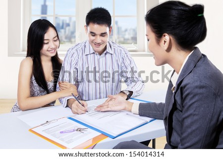 Young couple signing for financial contract with businesswoman - stock photo
