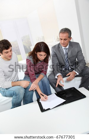 Young couple signing renting contract with real estate agent - stock photo