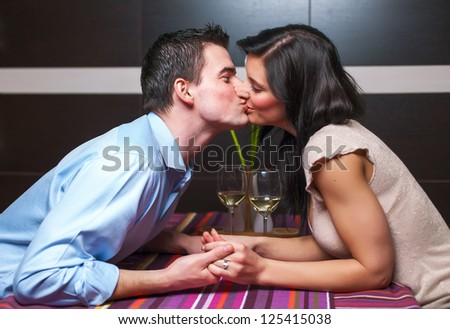 Young couple siiting in restaurant and kissing - stock photo
