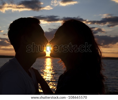 Young Couple Silhouette at Sunset - stock photo
