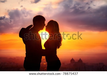 Young couple silhouette hugging and kissing outdoors at sunset background. Sun between them. Man with cowboy hat at his back - stock photo