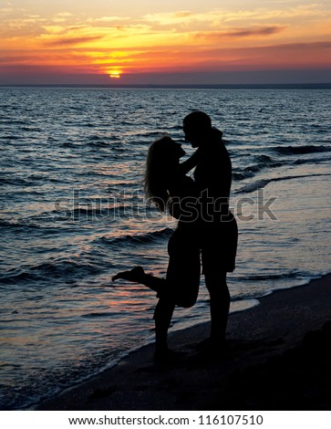 Young couple silhouette on a sea beach on sunset background - stock photo