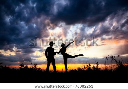Young couple silhouette outdoors at sunset dramatic sky background. Man in cowboy hat and woman dancing near by - stock photo