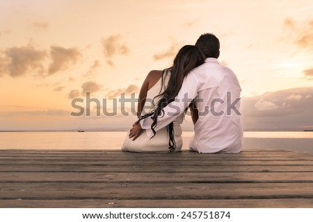 Young couple sit on the wood harbor