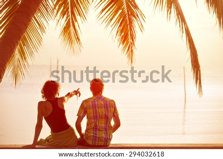 Young couple sit together under a palm tree and looking toward seaside. Girl pointing to something ahead - stock photo