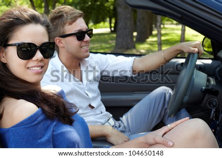 Young couple sits in the open top car, boy sits on the driver seat. - stock photo
