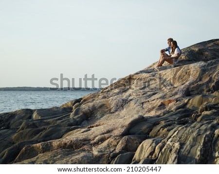 Young couple sits together on the cliff, rocky shore in archipelago