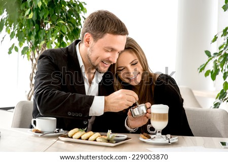 Young couple sitting and embracing at the restaurant - stock photo
