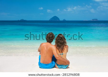 Young couple sitting and hugging on the tropical beach