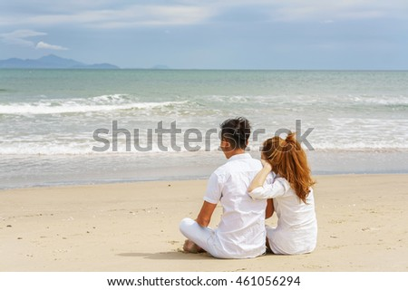 Young couple sitting and looking at the sea at the China Beach of Danang, in Vietnam