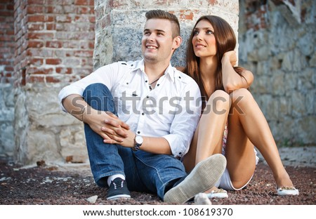 Young couple sitting and posing against brick frame building - stock photo