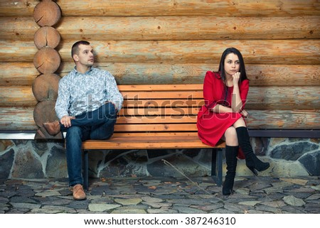 Young couple sitting apart on the bench - stock photo