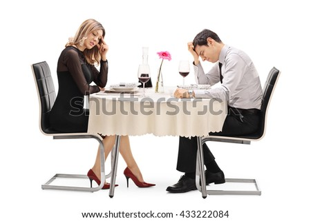 Young couple sitting at a table and arguing with each other isolated on white background - stock photo