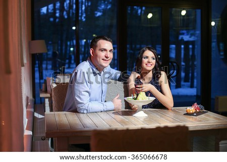 Young couple sitting at a table in a restaurant - stock photo