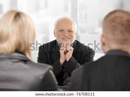 Young couple sitting at lawyer's office, senior lawyer looking at camera, smiling.? - stock photo