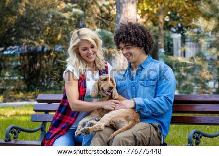 Young couple sitting at the bench in the park with his dog