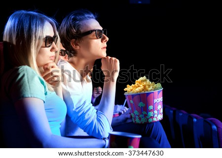 Young couple sitting at the cinema, watching a film. Cinema photo series - stock photo