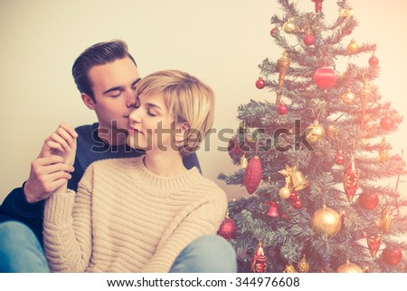 Young couple sitting beside Christmas tree  - stock photo
