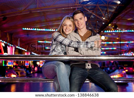 Young couple sitting by a bouncy cars ride while visiting an attractions park ground with their heads together and smiling with colorful lights in the background at night time. - stock photo