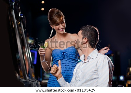 young couple sitting by the casino slot machine, looking happy to each other - stock photo