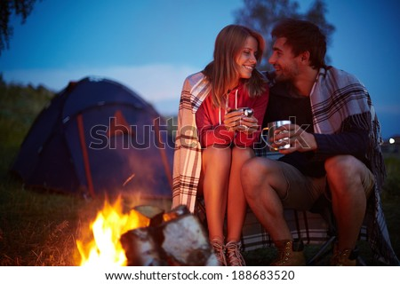 Young couple sitting by the fire and drinking tea outside - stock photo