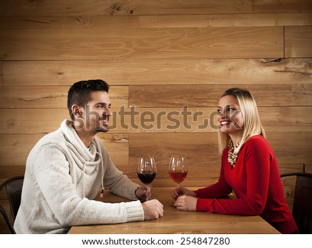 Young couple sitting in a bar drinking wine and talking - stock photo