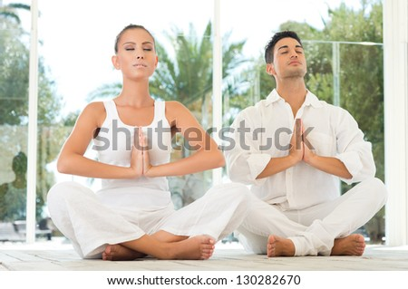 Young Couple Sitting In A Lotus Pose And Meditating While Exercising At Yoga - stock photo