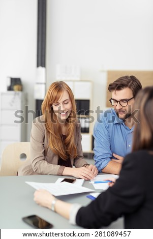 Young couple sitting in a meeting with an agent looking at a document together that she is presenting to them, view over the agents shoulder