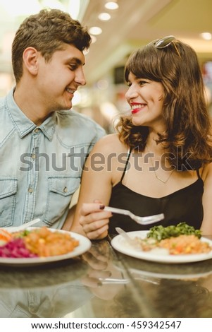 Young couple sitting in a restaurant, eating a common meal and looking at each other eyes